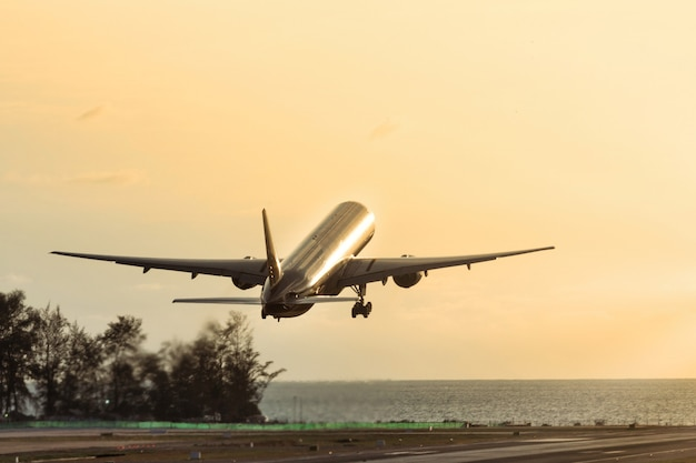 Passagiersvliegtuig opstijgen bij zonsondergang boven de zee. silhouet van vliegtuig vliegen omhoog. vakantie, luchtvaart, reisconcept
