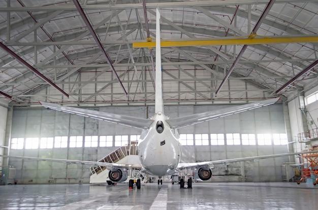 Passagiersvliegtuigen op onderhoud van motor en rompreparatie in de hangar van de luchthaven. achteraanzicht van de staart.