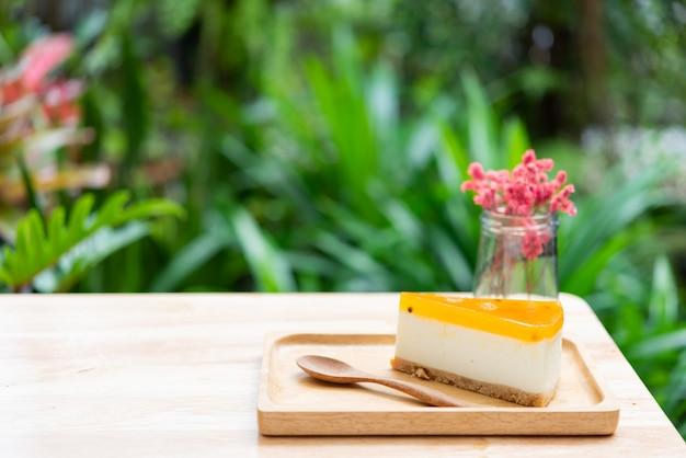 Passievruchten cheesecake serveren op hout tay en houten tafel met gedroogde bloemenvaas