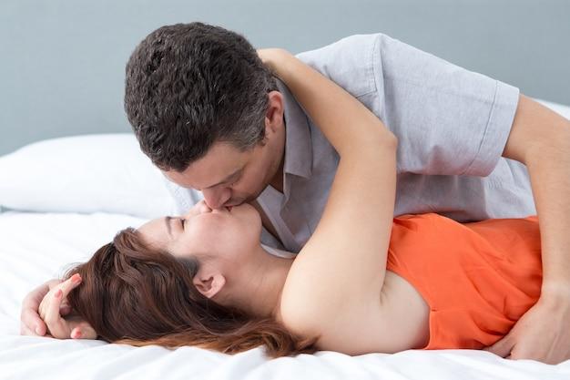 Passionate couple omhelzen en kussen in bed