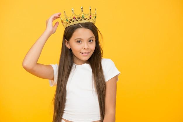 Past perfect. egoïstisch meisje draagt een gouden kroon. klein prinsesje. voel me kampioen. gelukkige jeugd. goed motivatieconcept. ze is een grote baas. trots op haar beloning. luxe en succes.
