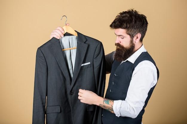 Past precies. maatwerk op maat. op maat gemaakt kostuumconcept. mode voor zakenmensen. op maat gemaakt pak. man bebaarde mode couturier kleermaker. elegant maatpak. maatwerk en kleding ontwerpen.