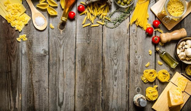 Pasta achtergrond. diverse soorten droge pasta met groenten, kaas en kruiden. op een houten tafel. vrije ruimte voor tekst. bovenaanzicht