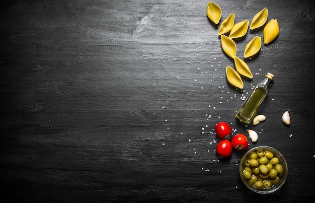 Pasta achtergrond droge pasta met olijfolie en tomaten op een zwarte houten achtergrond
