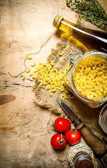 Pasta achtergrond. pasta met olijfolie, tomaten en zout.