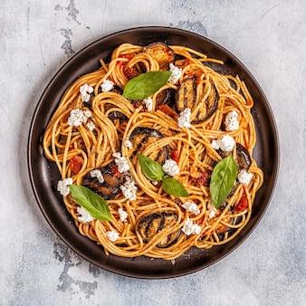 Pasta alla norma - traditioneel italiaans eten met aubergine, tomaat, kaas en basilicum