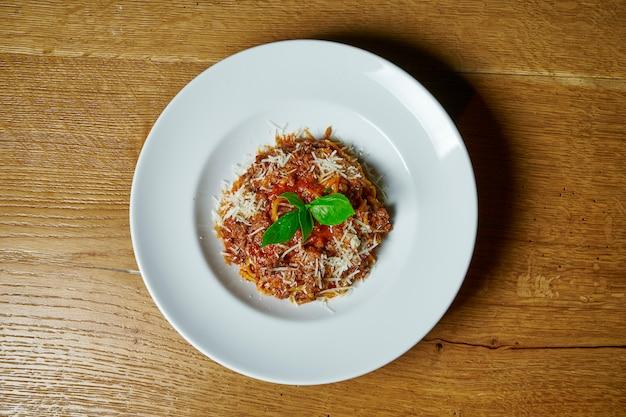 Pasta bolognese met gehakt, kaas en tomatensaus in een witte plaat op houten tafel. bovenaanzicht eten. italiaanse keuken