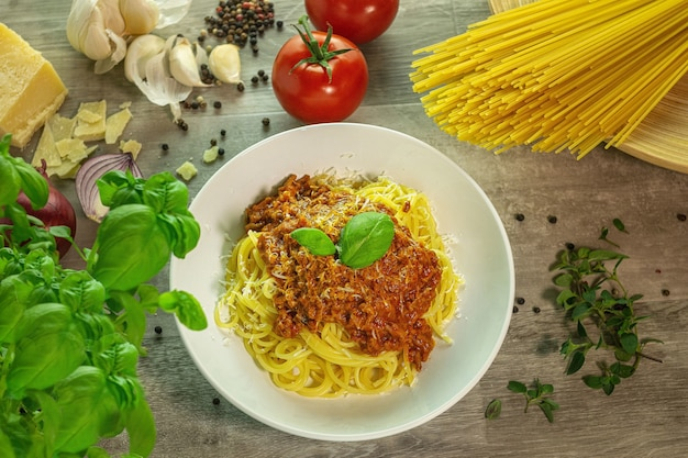 Pasta bolognese met ingrediënten op een houten tafel