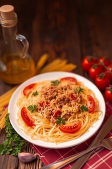 Pasta bolognese met tomatensaus en gehakt, geraspte parmezaanse kaas en verse peterselie - zelfgemaakte gezonde italiaanse pasta