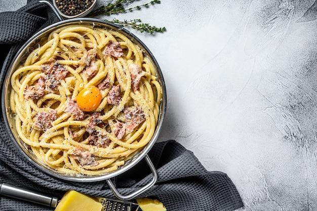Pasta carbonara, bucatini in de pan. bovenaanzicht. kopieer ruimte