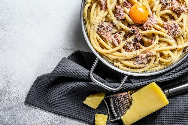 Pasta carbonara, bucatini in de pan. grijze achtergrond. bovenaanzicht. kopieer ruimte