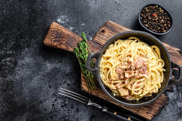 Pasta carbonara met spek en parmezaan in een pan
