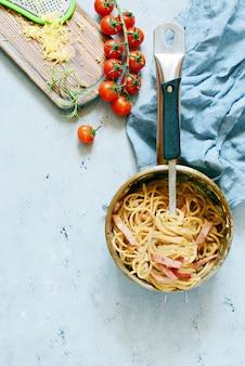 Pasta carbonara met spek en parmezaanse kaas in grijze platen op tafel, restaurant serveren op een blauwe muur. traditionele italiaanse keuken. thuis familiediner bekijk van bovenaf