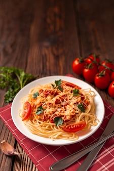 Pasta carbonara met tomatensaus en gehakt, geraspte parmezaanse kaas en verse peterselie