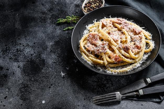 Pasta carbonara op zwarte plaat met parmezaanse kaas, bucatini. bovenaanzicht. kopieer ruimte