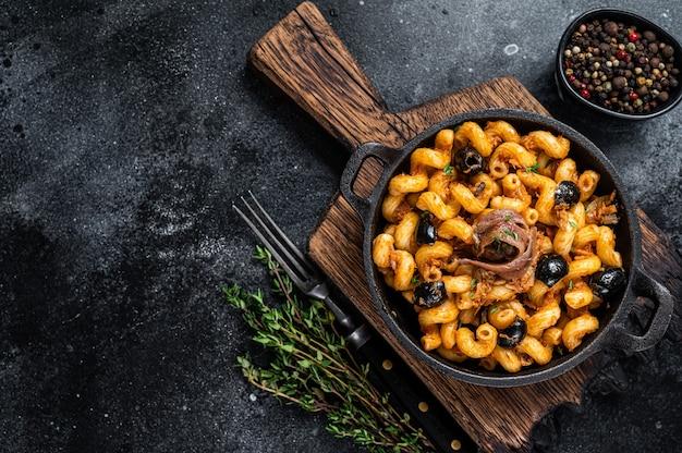Pasta cellentani puttanesca pasta met zeevruchten in een pan