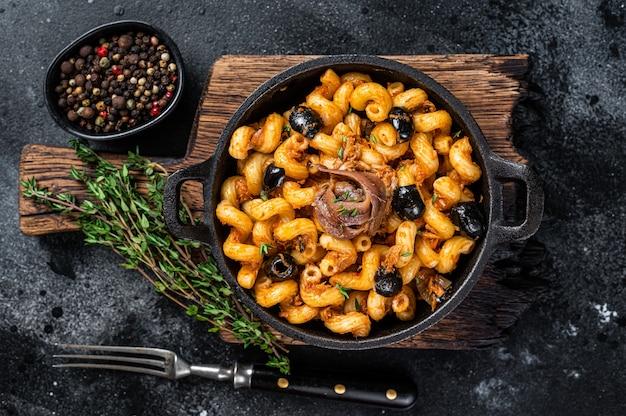Pasta cellentani puttanesca zeevruchten pasta in een pan. zwarte achtergrond. bovenaanzicht.