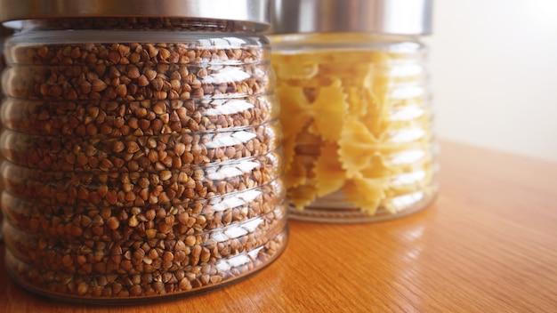 Pasta en boekweitmaaltijden. gezond koken in glazen potcontainers op houten tafel. uitgebalanceerd dieetvoedsel.