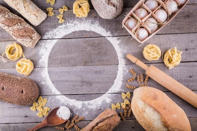 Pasta en brood op houten achtergrond. bovenaanzicht met kopie ruimte. ingrediënten voor bakkerijproducten