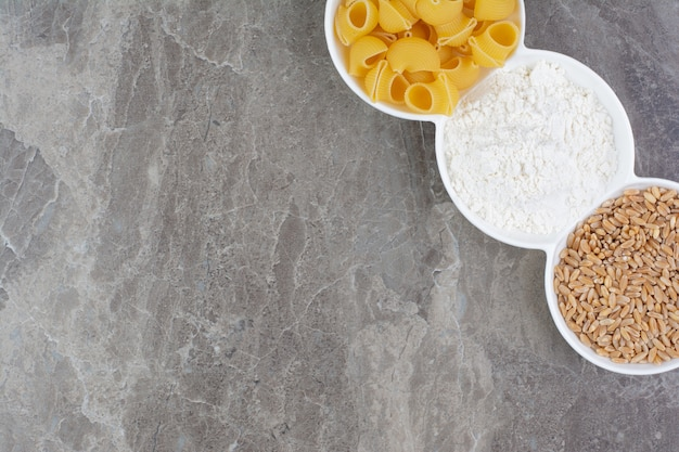 Pasta en ingrediënten in witte ceramische kopjes.