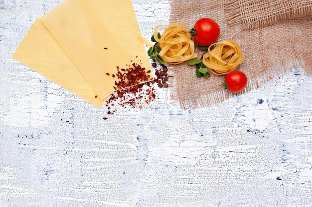 Pasta en ingrediënten op houten achtergrond met kopie ruimte. bovenaanzicht