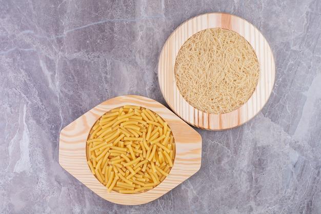 Pasta en rijst in keramische kopjes op het blauwe marmer.