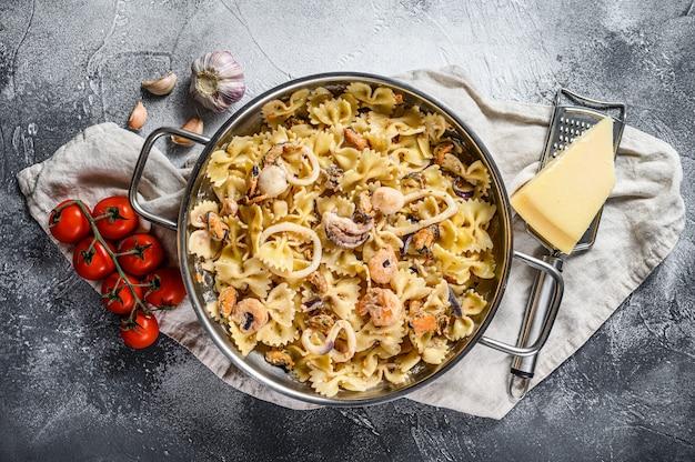 Pasta farfale met zeevruchten, octopus, garnalen, inktvis, sint-jakobsschelp en mosselen. bovenaanzicht