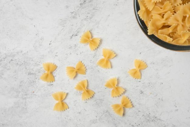Pasta farfalle in glazen kom op witte achtergrond.