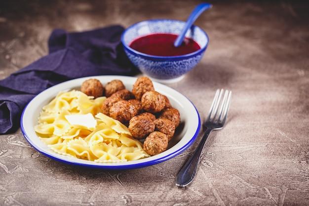 Pasta farfalle met gehaktballetjes en cranberrysaus met kruiden en specerijen rozemarijn, kaneel en anijs.