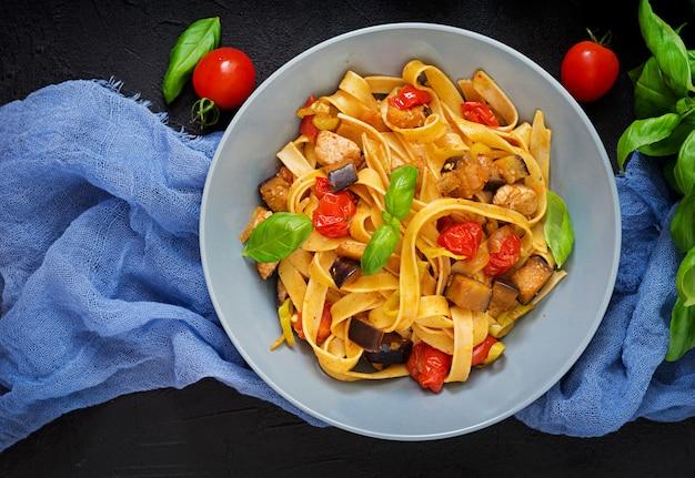 Pasta fettuccine met tomaat, aubergine en kipfilet in kom. plat leggen.