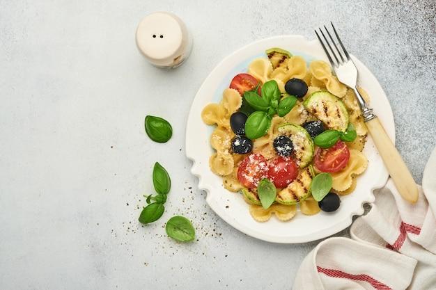 Pasta fiocchi salade met groenten gegrilde courgette, cherrytomaat, olijven, basilicum en parmezaanse kaas in witte plaat op lichte leisteen, steen of betonnen ondergrond. lunchconcept. bovenaanzicht