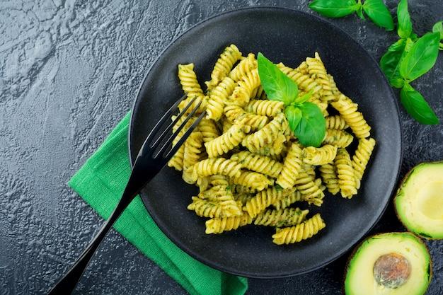 Pasta fusilli met groene avocado basilicum saus en ingrediënten op zwarte tafel. bovenaanzicht. kopieer ruimte.