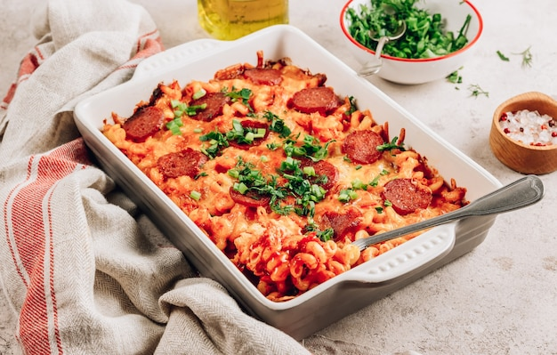 Pasta gebakken in een tomatenpestosaus met kaas, kruiden en pepperoni. pittige pizza pasta