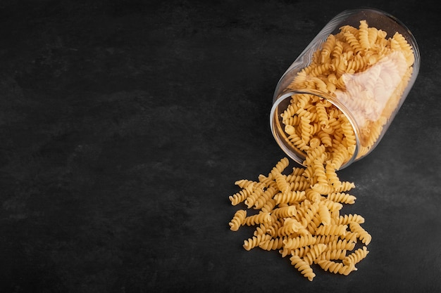Pasta geïsoleerd op zwarte achtergrond uit een glazen pot.
