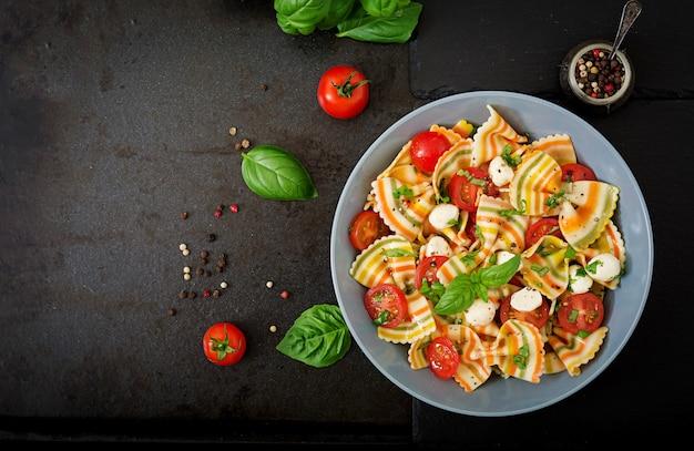 Pasta gekleurde farfalle salade met tomaten, mozzarella en basilicum.