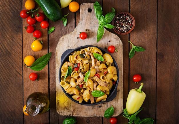 Pasta gomiti rigati met vlees en groenten in aziatische stijl.