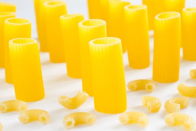 Pasta in de vorm van buizen en kleine hoorns op een witte achtergrond