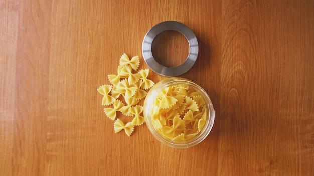 Pasta in de vorm van strikken die uit glazen pot worden verspreid. italiaanse handgemaakte pasta op het houten oppervlak.