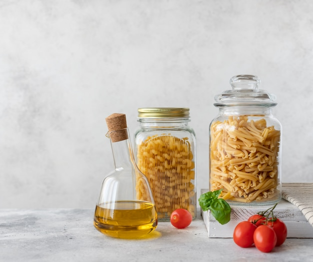 Pasta in een glazen pot en olijfolie in een fles