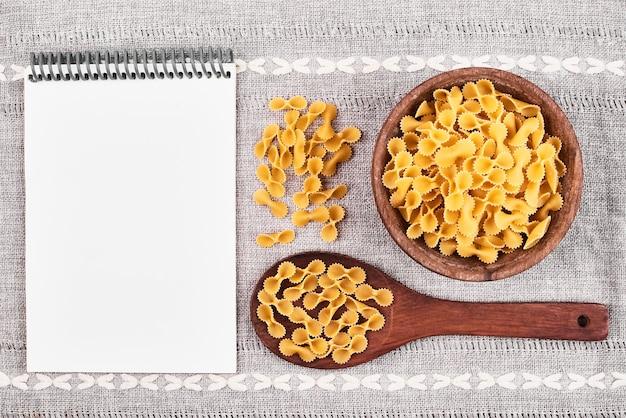 Pasta in een houten lepel met een receptenboek opzij.