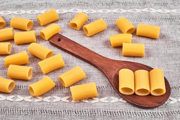 Pasta in een houten lepel op keukenpapier.