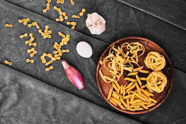 Pasta in een houten schotel met groenten.