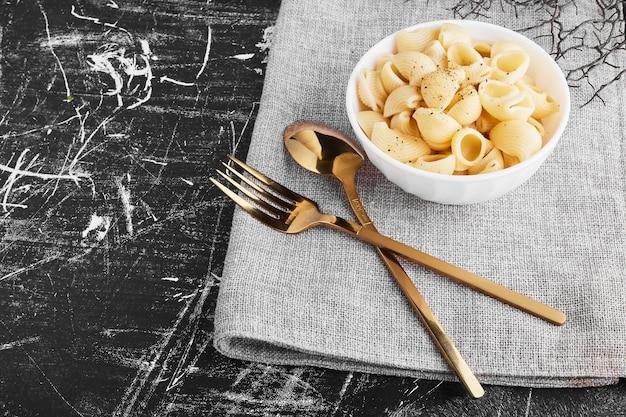 Pasta in een keramische beker met bestekset.