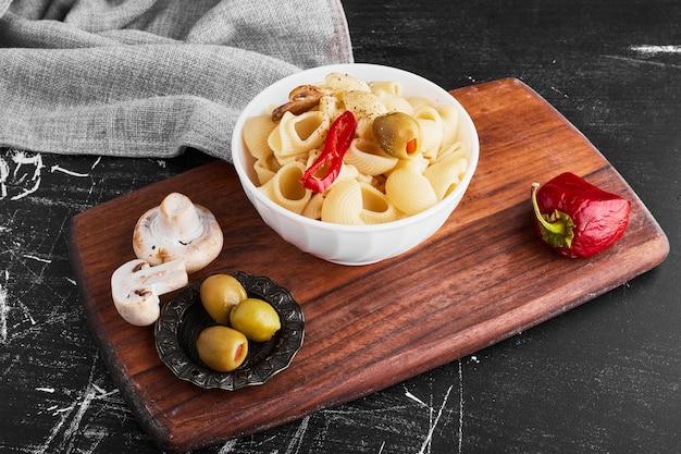 Pasta in een keramische beker met ingrediënten.