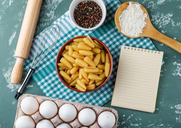 Pasta in een kom met eieren, zetmeel, peperkorrels, garde, deegroller en schrijfboek