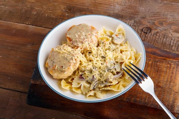 Pasta in een romige saus met champignons en kippengehaktballetjes in een beige plaat op een houten tafel met een vork horizontale foto