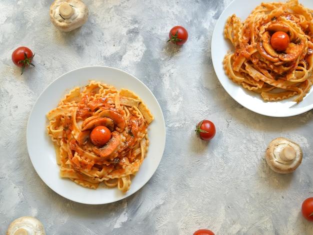 Pasta in een witte plaat. pasta met cherrytomaatjes en champignons. bovenaanzicht. vrije ruimte voor tekst.
