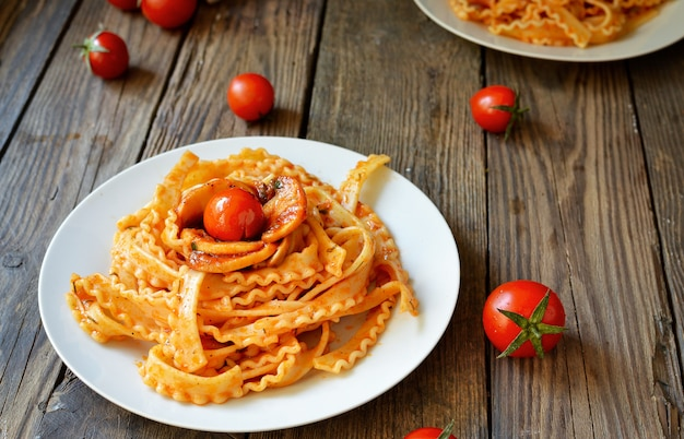 Pasta in een witte plaat. pasta met tomatensaus, champignons met kerstomaatjes