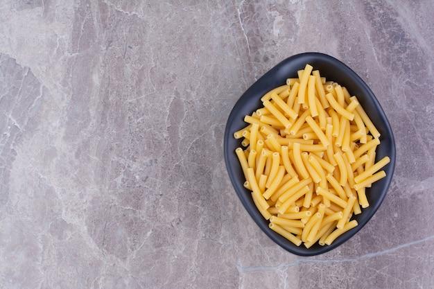 Pasta in een zwarte keramische schotel op het marmer