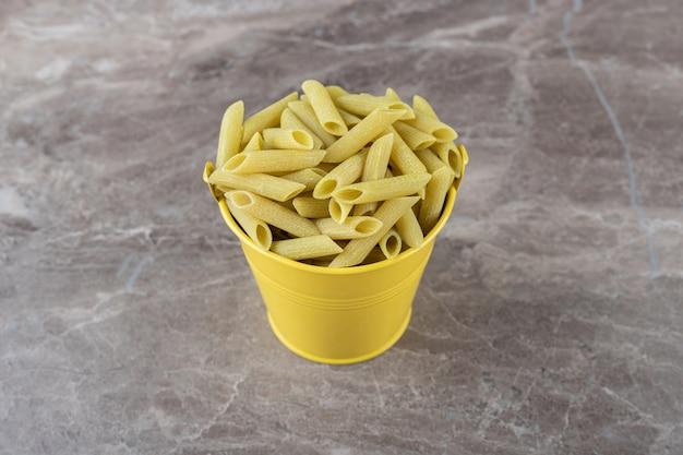 Pasta in gele emmer, op het marmeren oppervlak.
